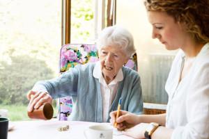 oudere vrouw en verzorgende doen een spel