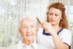 oudere dame met verzorgende die haar haar borstelt