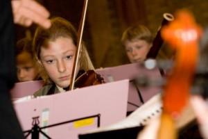 jonge violiste tijdens uitvoering jeugdorkest
